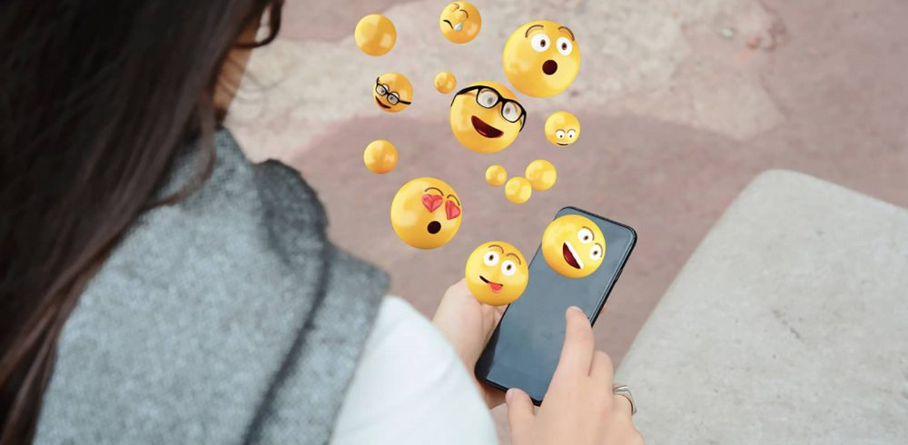 woman using smartphone sending emojis.